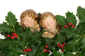 Angel figurines with green holly leaves and red berries — Stock Photo