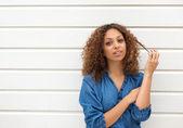 Mooie jonge vrouw op zoek naar camera met hand in haar — Stockfoto