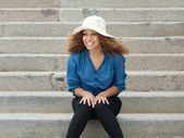 Carefree young woman wearing hat sitting on stairs — Stock Photo