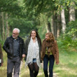 Mother and father enjoying a walk through the woods with daughters — Stock Photo #33425829