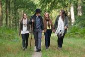 Happy family enjoying a stroll through the woods — Stock Photo