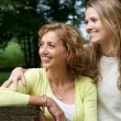 Portrait of a mother and daughter smiling outdoors — Stock Photo
