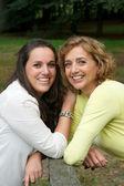 Kızı ile birlikte gülümseyerek mutlu bir anne portresi — Stok fotoğraf