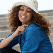 Beautiful young woman laughing outdoors with hat — Stock Photo