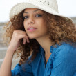 Portrait of an attractive young woman sitting outdoors with hat — Stock Photo
