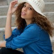 Portrait of a pretty woman sitting outdoors with hat — Stockfoto