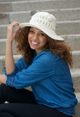 Happy young woman smiling outdoors with hat — Stock Photo