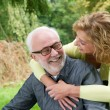 Older man and woman smiling outdoors — Stock Photo