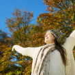 Carefree woman enjoying autumn sun with arms outstretched — Stock Photo #34868383