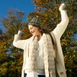 Cheerful woman smiling outdoors on a sunny fall day with arms outstretched — Stock Photo #34868447