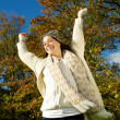 Beautiful young woman smiling outdoors with arms outstretched — Stock Photo