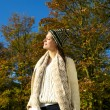 Attractive woman in sweater and hat enjoying the sun on an autumn calm day — Stock Photo #34868461