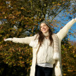 Happy young woman standing outdoors with arms outstretched — Stock Photo