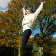 Young woman jumping for joy outdoors on a beautiful fall day — Stock Photo