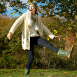 Carefree young woman kicking puddle of water in the park — Stock Photo