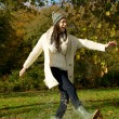 Young woman walking in the park and kicking a puddle of water — Stock Photo #34959447
