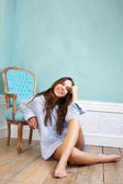 Happy young woman sitting on wood floor and relaxing at home — Stock Photo