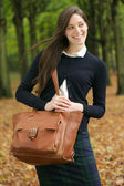 Beautiful young woman walking outdoors with bag on an autumn day — Stock Photo