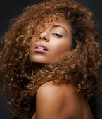 Beauty portrait of a female fashion model with curly hair — Stock Photo