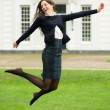 Carefree young woman jumping outdoors — Stock Photo