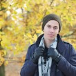 Handsome young man standing outdoors with jacket hat scarf and gloves — Stock Photo