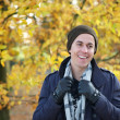 Portrait of a young man smiling outdoors in jacket gloves hat scarf — Stock Photo