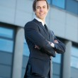 Young business man smiling outdoors with arms crossed — Stock Photo