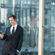 Portrait of a businessman smiling and looking at mobile phone outdoors — Stock Photo