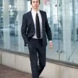 Young businessman walking on sidewalk in a suit — Stock Photo
