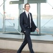 Portrait of a handsome young businessman walking in the city — Stock Photo