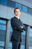 Confident young businessman standing outdoors with arms crossed — Stock Photo