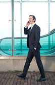 Portrait of a businessman walking and talking on mobile phone — Stock Photo