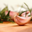Garlic clove with fresh rosemary in background — Stock Photo