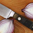 Close up knife with two slices of red onion on cutting board — Stock Photo #37002565
