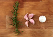 Cloves of garlic and fresh organic rosemary on wooden chopping board — Stock Photo