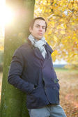 Relaxed man standing outdoors in park on Autumn day — Stock Photo
