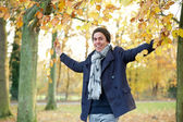 Happy man smiling and holding tree branches with yellow leaves outdoors — Stock Photo
