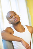Portrait of a young man posing by window — Stock Photo
