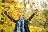 Happy smiling man throwing leaves with open arms in autumn — Stock Photo