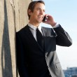 Businessman relaxing and talking on mobile phone outdoors — Stock Photo #37389021