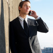 Attractive businessman talking on cellphone outdoors — Stock Photo