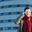 Attractive smiling man talking on mobile phone outdoors — Stock Photo