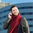 Cheerful man talking on mobile phone in the city — Stock Photo