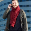 Smiling man talking on mobile phone outside building — Stock Photo #38424333