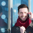 Handsome young man smiling and calling by mobile phone outdoors — Stock Photo