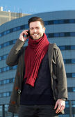 Smiling man talking on mobile phone outside building — Stock Photo