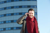 Cheerful young man talking on mobile phone in the city — Stock Photo