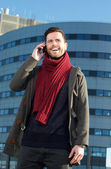 Happy young man talking on cellphone in the city — Stock Photo