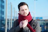 Young man with beard posing with scarf outdoors — Stock Photo