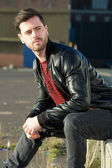 Male fashion model sitting outdoors with jeans and black jacket — Stok fotoğraf